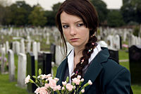 A portrait of April, a teenage girl dressed in a school uniform, walking through a graveyard, holding flowers