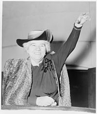 Photo of Elizabeth Kenny, with short white hair, smiling and waving at age 70