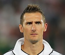 Photographic portrait of Klose's face and shoulders. He is wearing a white tracksuit top.