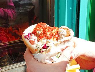 L'As du Fallafel - A patron of L'As du Fallafel holding the restaurant's acclaimed falafel sandwich covered in hot sauce.