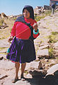 Female on Taquile island shows drop spindle.jpg