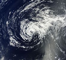 A satellite image depicts the tropical cyclone over the open waters as a spiral of patchy low-level clouds, devoid of strong thunderstorms.