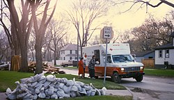 Several people are collecting items from an American Red Cross vehicle in a neighborhood. Around the neighborhood is piles of damaged possessions and sandbags.