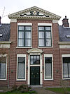 foto van Voormalig landhuis met door fronton gedekte verhoogde middenpartij gevat tussen pilasters