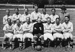 An association football team poses for a formative black-and-white photograph. A row of seven men sits on a bench, all wearing light-coloured shirts and white shorts apart from the player in the centre, who wears black. A football rests on the ground between his feet. Behind the seated row stand seven more men, all but one of whom are wearing the same light-coloured shirts. The exception is a gentleman standing at the end of the row on the viewer's right, who wears a dark double-breasted suit, tie and wide-brimmed fedora hat. All of those present have their arms folded apart from the man in the suit, whose hands are behind his back. In the background a set of goalposts can be seen.