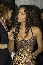 Upper body shot of Halle Berry dressed in brown and gold evening gown and holding an autograph pen.
