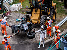 Picture of a damaged silver Formula One car being removed from the track