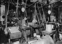 Photograph of a large workshop crowded with machinery. There are at least four men working there. There are belts coming down from the ceiling that drive the machinery. Two electric lighting fixtures are also hung from the ceiling.