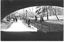 An underpass in Central Park with people walking and horseback riding