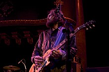 Huw Bunford playing guitar while looking to his right, away from the camera. The guitarist has a large beard and is wearing a brown jacket.
