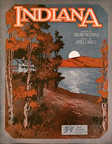 "Sheet music cover showing a white house in a forest by a lake. The forest is orange and brown, and the sky is dark blue. On the other side of the lake, the moon is rising. The word ""Indiana"" is written at the top of the poster. Underneath it, there is a text ""Words by Ballard MacDonald, music by James F. Hanley""."