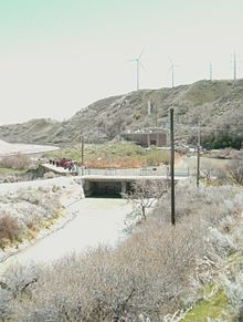 A narrow canyon with a river flowing through it. Railroad tracks are on the left side of the river. A building is on the right side.