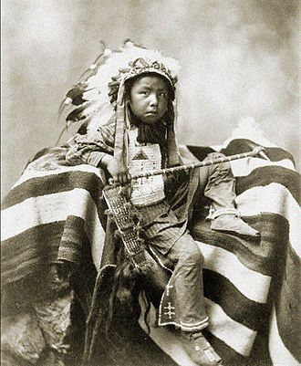 "Trans-Mississippi Exposition - A young Sioux boy poses with a club while part of a ""living display"" at the Exposition"