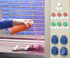 Dye penetrant inspection - Application of the penetrant to a part in a ventilated test area.