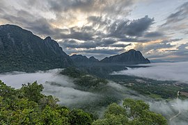 Karst mountains colorful clouds and mist at sunrise from the top of Mount Nam Xay Vang Vieng Laos.jpg