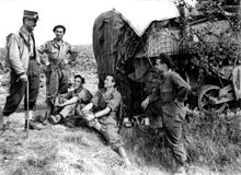 A man in uniform carrying a walking stick and wearing a kepi talks to four men in overalls wearing berets. A heavily camouflaged tank is in the background.