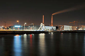 Les Bains Des Docks - View of the building at night from across the water.