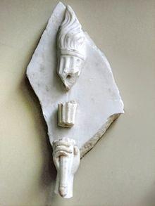 Plaque de marbre avec une main portant une torche, avec 2 morceaux manquants.