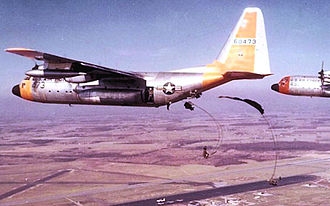 21st Airlift Squadron - Lockheed C-130A-6-LM Hercules, 56-473, performing a parachute drop, with 56-493 in the distance.