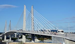 Tilikum Crossing - Viewed from the west with a MAX train and a bus crossing the bridge