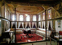 Room with many stained-glass windows, small table in center and seating along the walls
