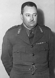 A black and white photograph of the upper body and head of a middle-aged Caucasian man. He is wearing the uniform of an Australian Army officer, has short dark hair and a small neatly cropped moustache on his upper lip.