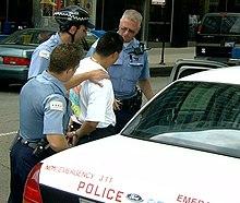 tri policistoj ĉirkaŭas viron en ekdrajvejĉemizo kiu estas mankatenita