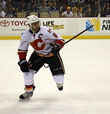 Giordano skates toward the camera as he observes the play off to his left.