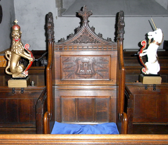 """Mayor of Barnstaple - The Mayor's Pew, St Peter's Church, Barnstaple. On the chair back are shown the arms of Barnstaple: Gules a castle of three towers conjoined argent the centre tower larger than the others, between two scrolls inscribed in Latin: Domini Nomen and Firmum Castellum (""""The Name of God (is) a Strong Castle"""")"""