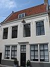 foto van Huis met brede gecementeerde rechte gevel en zijtopgevel met vlechtingen