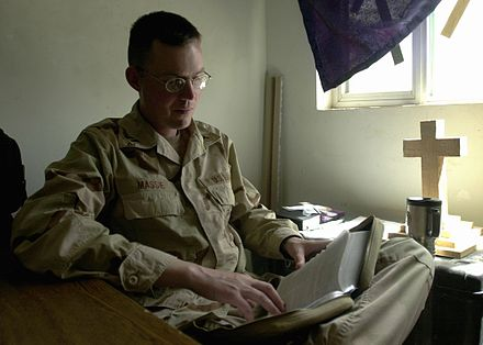 A U.S. Navy chaplain in Iraq studies his Bible for an upcoming service. Military chaplain.jpg