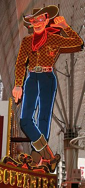 Photograph of a large painted sign in the form of a cowboy. The cowboy is winking his eye. His left hand is lifted, and he's pointing that thumb towards the building to his right. A lighted cigarette dangles from the corner of his mouth. He's wearing a cowboy hat, boots, and a scarf. Glowing neon tubes highlight the outlines.