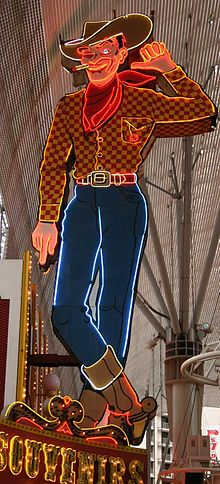 Photograph of a large painted sign in the form of a cowboy. The cowboy is winking one eye. His left hand is lifted, and he's pointing that thumb towards the building to his right. A lighted cigarette dangles from the corner of his mouth. He's wearing a cowboy hat, boots, and a scarf. Glowing neon tubes highlight the outlines.