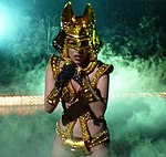 A woman in a shiny gold outfit, with golden gloves and a golden headress with two protrusions from the sides. Behind the woman, smoke can be seen billowing around.