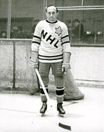 "An ice hockey player stands on an ice rink. He is wearing a sweater that has the letters ""NHL"" in a downward diagonal with a large star on his left shoulder."