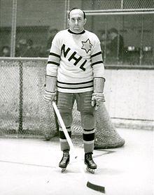 Photo de Morenz devant un but dans un chandail blanc marqué des lettres NHL.