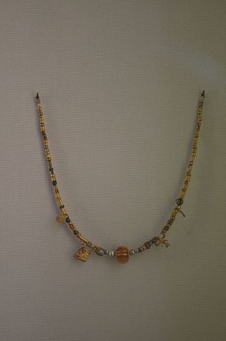 pearl neklace ornated with a pendant in the shape of a horned lion