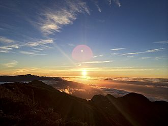 Pedra da Mina - Sunrise seen from the top of Pedra da Mina. The Itatiaia Massif can be seen to the left in the background. Its highest summit, visible in the picture, is Pico das Agulhas Negras, which until 2000 was thought to be the highest point of the Mantiqueira Mountains, but was then found to be actually about 7 metres (23 ft) lower than Pedra da Mina. The two peaks are approximately 20 km (12 mi) apart as the crow flies.