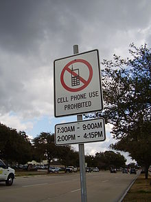 mobile phone  a sign along bellaire boulevard in southside place texas greater houston states that using mobile phones while driving is prohibited from 7 30 am to 9 00