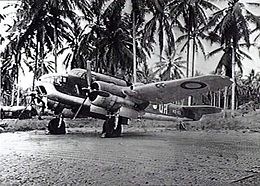 Three-quarter view of twin-engined military aircraft on jungle landing