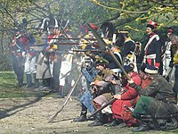 A group of reenactors dressed in Polish 18th century uniforms and szlachta civilian attire firing a musket volley.
