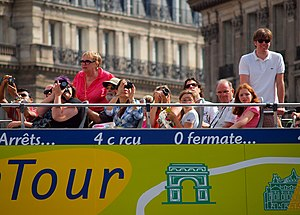 Tour bus service - Tourists taking photos from a ParisCityVision open-topped tour bus in Paris.