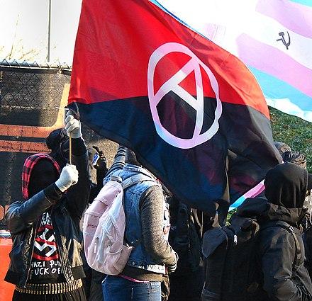 2017年の愛国者の祈りに抗議して修正されたアナキスト赤と黒の旗とトランスジェンダープライドフラグを持つローズシティアンティファ活動家