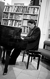 Philip Glass de profil assis jouant au piano