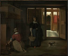 Interior of a Dutch house with a woman kneeling by a fire conversing with a woman standing