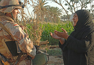 Original caption: A woman pleads to an Iraqi a...