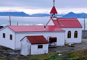 Nach dem verheerenden Brand von 1994 neu errichtete katholische Kirche von Pond Inlet; auf der gegenüberliegenden Seite des Eclipse Sound: Bylot Island