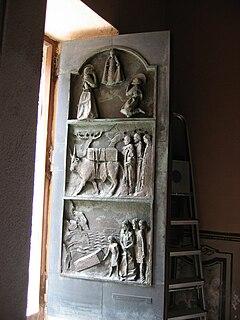 La porta Santa in bronzo della basilica di Luogosanto, opera dello scultore Luca Luchetti, aperta. I tre quadri raccontano la storia della chiesa stessa, legata al culto di Maria bambina e riferita ad una apparizione della stessa.