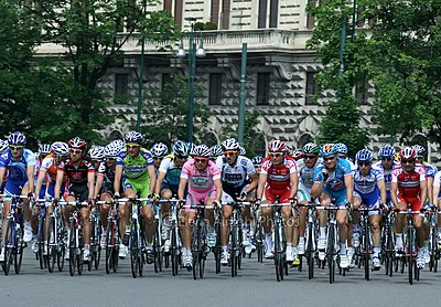 Cyclists from many teams riding in the streets. A building, streetlamps and trees are shown in the background.