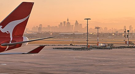 Tail of a Qantas Boeing 747-400 at Sydney Airport with the skyline of Sydney in the background. QantasSYD.jpg